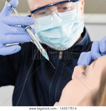 Female patient receiving dental anesthetic , toned image