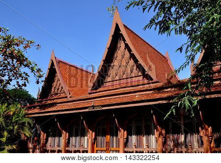 Sampan Thailand - January 10 2010: Wooden dining pavilion with high Thai roofs and decorative ornamentation at the Riverside Rose Garden and Park