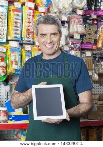 Salesman Showing Digital Tablet With Blank Screen In Pet Store