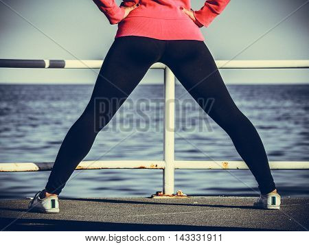 Sports and activities. Part body of training active sporty girl outside. Slim fit legs on seaside. poster