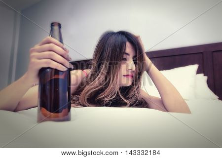 Drunk woman on the bed with bottle in hand