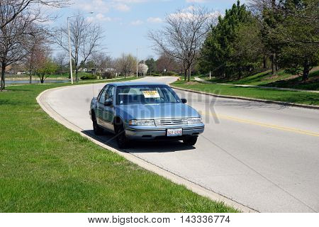 JOLIET, ILLINOIS / UNITED STATES - APRIL 19, 2016: A sign on the windshield of a blue automobile, parked on the Wesmere Country Club's Wesmere Parkway, indicates the direction of a garage sale.