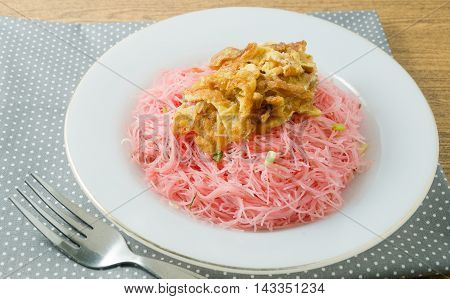 Thai Cuisine and Food Delicious Red Stir Fried Rice Vermicelli Served with Julienne Omelet and Chopped Scallion.
