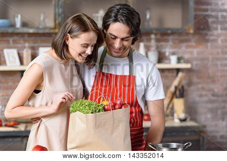 Happy married couple is satisfied with bought vegetables. They are looking into packet and smiling. Man and woman are standing in kitchen and embracing