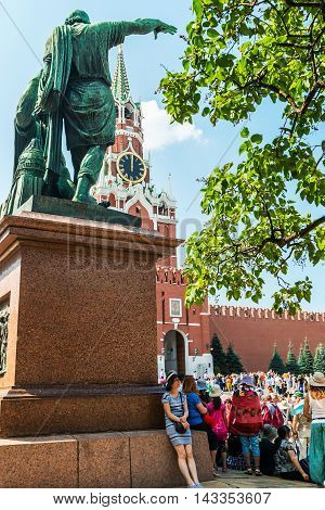 Moscow, Russia - August 7, 2016: Kremlin clock chimes can be seen through the monument to Minin and Pozharsky in Moscow, St. Basil Cathedral.