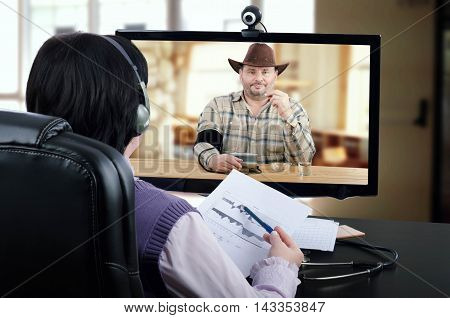 Virtual female doctor in headset reviews blood pressure graph with online patient in monitor. Bearded cowboy in checkered shirt, brown hat sits at wooden desk, holds a pill by left hand checks his blood pressure and looks directly at the physician