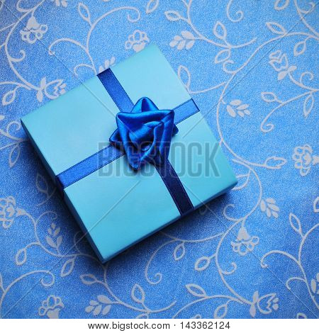 Beautiful blue Gift box with bow over blue fabric background
