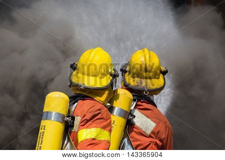 two firefighter in fire fighting suit spray water to fire and black smoke