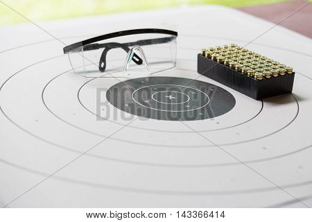 paper shooting target with safety glasses and 9 mm bullet for shooting practice in law enforcement academy shooting range focus on 'X'