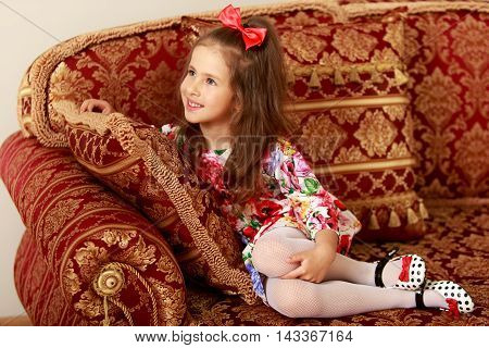 Nice little girl with a long ponytail down to his shoulders, and a red bow on her head, in a beautiful summer dress sitting on the couch. The girl looks away from the camera