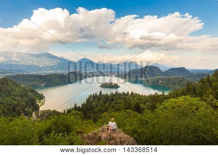 Relaxed female traveler enjoying beautiful panoramic view of Julian Alps, Lake Bled with St. Marys Church of the Assumption on the small island, Bled, Slovenia, Europe.