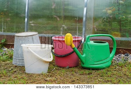 Buckets and watering pot near the hothouse