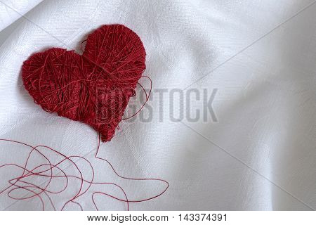 red fabric heart on white background with the wire tattered, white background, natural light
