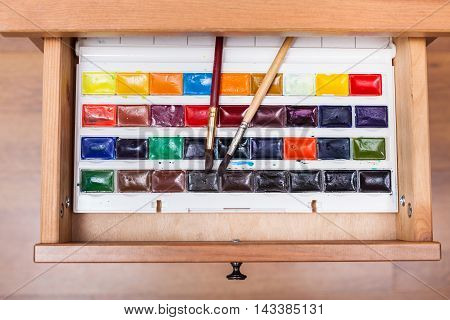 Box With Watercolor Paints And Brushes In Drawer