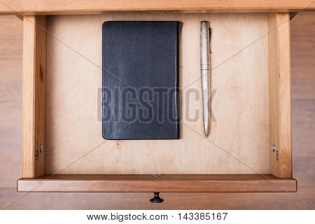 Silver Pen And Black Notebook In Open Drawer