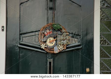 Classic christmas wreath with decorations on a wooden door