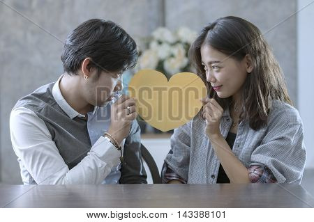 couples of asian man and woman holding heart shape paper cut with happiness emotion peple love conceptual