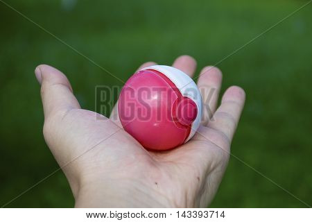 Thailand - August 20, 2016: Poke ball in Hand  (Pokemon Ball). Pokeball toy of the game Pokemon Go at Chon Buri, Thailand.