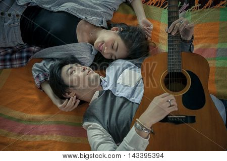 couples of asian younger man and woman playing guitar with relaxing and happiness emotion