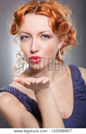 Beautiful Young Woman Sends A Kiss In The Air. Isolated On A Gra