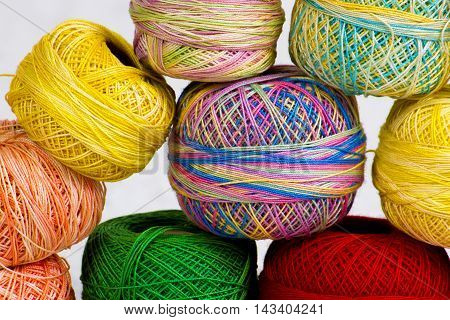 A detail image of a pile of colorful tatting yarn for crochet and making lace.