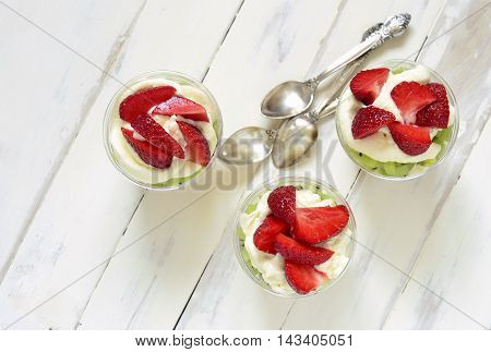 Layered dessert with strawberries kiwi biscuit and cream, Trifle, top view
