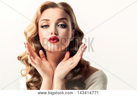 Beautiful woman looks like a star of a retro movie . Vintage pin-up girl send air kiss . Model with curly hair and bright makeup with red lips.
