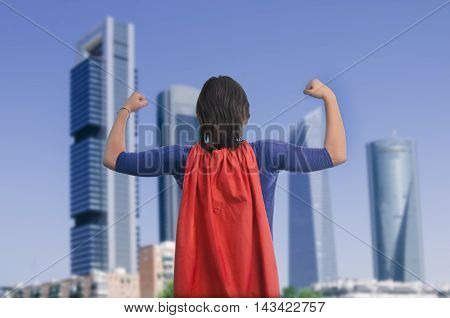 Woman Superhero With Red Cape In Strong Position In Front Of A Buildings