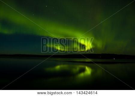 emerald green northern lights refection on lake