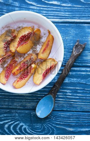 A delicious healthy and nutritious breakfast with yogurt and peach on blue wooden background