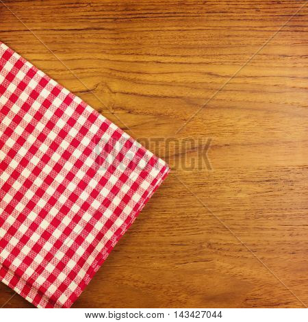 Empty wooden table with red checked tablecloth