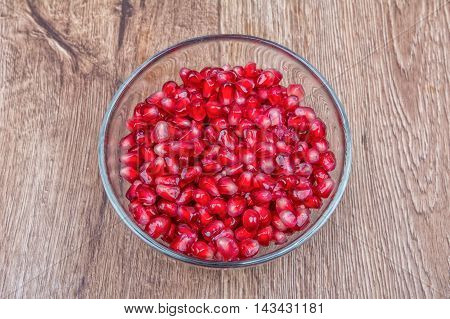 Fresh organic pomegranate seeds in a bowl on a wooden background poster