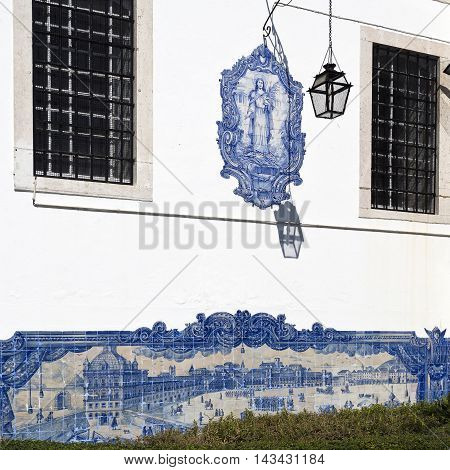 LISBON, PORTUGAL - September 30, 2015: An outside wall of the church with two tile panels, one of Comercio Square before the 1755 quake, another of Santa Luzia, the patron saint of the church in Lisbon, Portugal on September 30, 2015 in Lisbon, Portugal