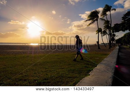 Honolulu, Hawaii, USA - Dec 21, 2015: Setting sun over beach at Ala Moana Park, along Ala Moana Park Drive. The beach overlooks Mamala Bay and features some flares. A person walks on the grass in silhouette with a skateboard in hand.