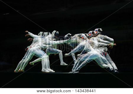 RIO DE JANEIRO, BRAZIL - AUGUST 10, 2016: Russian fencer (L)  attacks Great Britain fencer at the Men's team foil semifinal of the Rio 2016 Olympic Games at the Carioca Arena 3 (multiple  exposures)