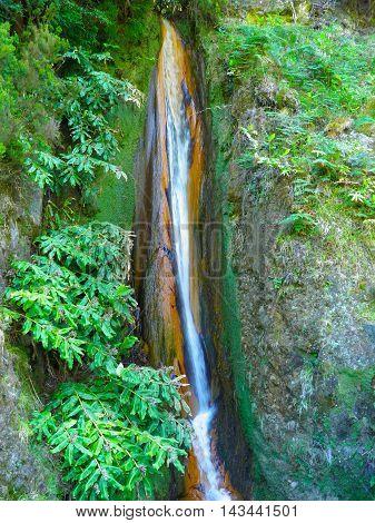 Colorful waterfall near Furnas Azores. Waterfall on volcanic Sao Miguel Island Portugal.