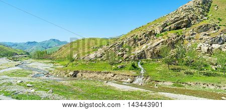 The narrow twisted river flows along the rocky valley between Zarafshan and Gissar mountain ranges of Pamir-Alay the cows graze on the hills Uzbekistan.