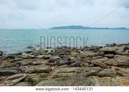 Rocks on shoreline with sea and mountain background at Khao Laem Ya Mu Ko Samet National Park in Thailand.