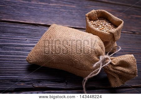 Fresh bread, baked goods, harvest on the farm, delicious food, burlap sack of grain, healthy food, a table of old wood, close-up corn, wheat grain spillage