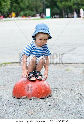 Baby Sitting On Concrete Hemisphere