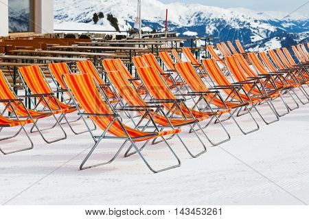 Photo of empty red deckchairs on the mountain in the Alps