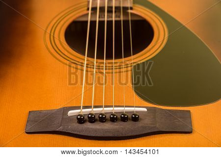 Close up of an acoustic guitar with focus on the bridge