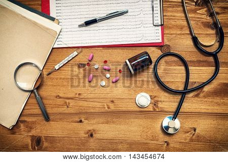 Doctor's work desk as copy space. General medical practitioner workspace with assorted office supplies such as stethoscope loupe thermometer pencil tablets and pills top view.