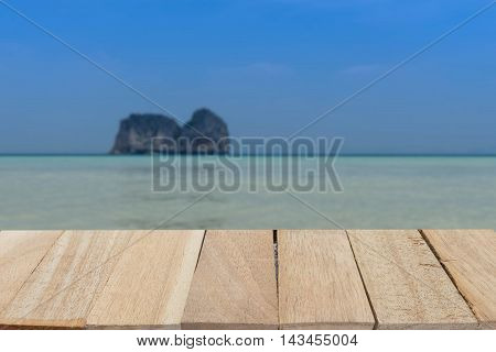 wood table top on blur of seascape and island on bluesky view - can use to display or montage on product