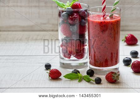 A glass of smoothie with berries and a glass of ingredients strawberries, raspberries, blueberries near scattered berries, straws on white wood background. Berry smoothie and ingredients. Horizontal.
