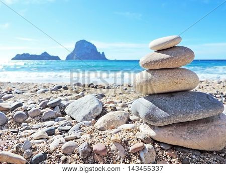 Balanced stone stack or stack rock at the beach of Cala DHort, ibiza Island with view to Es Vedra.