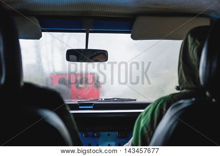 Adventure off road car in rainy hazy environment, view from inside car, selective focus