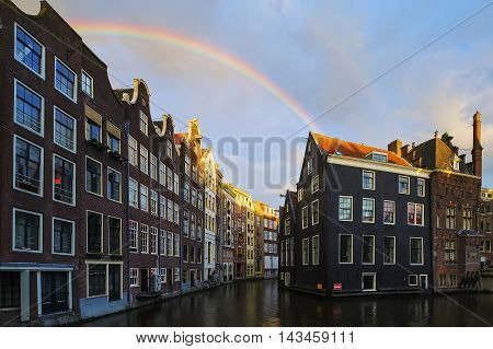 Famous Amsterdam canal with beautiful rainbow, Netherlands