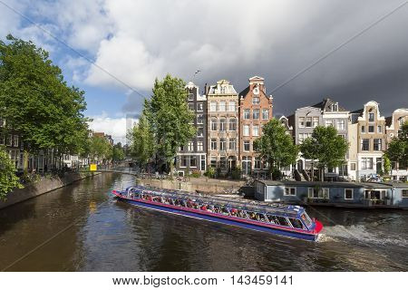 AMSTERDAM NETHARLANDS - JULY 5 2016 : tourists in cruise boat at Amsterdam canal Netherlands.