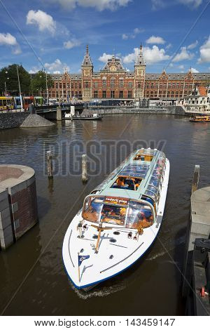 Amsterdam Netherlands JULY 6 2016: canal cruise boat in front of amsterdam central railway station